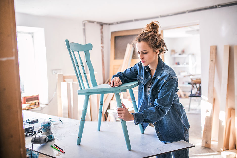 Woman Sanding a chair